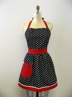 This is a very cute vintage inspired full apron! This apron is in a black and white polka dot print. The pocket and straps are in a solid red with white ric-rac trim on bottom band.