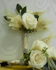 Small bridesmaid bouquets with white peacock feathers and rhinestone banding.