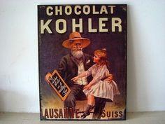 """Plaque murale représentant une publicité ancienne pour du chocolat avec comme impression """"Chocolat Kohler"""". Elle représente une fillette sur les genoux de son grand père Cette plaque murale aspect rétro réhaussera avec charme la déco cuisine rétro de votre intérieur. Dimensions : 26.5 cm sur 35 cm  http://www.decoacoeur.com/deco-cuisine/1542-plaque-retro-chocolat-kohler-deco-cuisine-.html"""