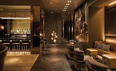 Hotel lounge - chevron wood flooring, large-scale old photograph, brass trellis with accent lighting above the bar, soft warm glow.