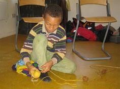 A class three child unravels his wool prior to knitting.