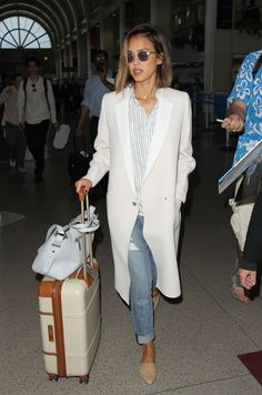 Airport Chic 101: Travel Style Stars. Jessica Alba.  Alba's cuffed boyfriend jeans, Madewell striped shirt and long-line Gerard Darel Catia are complemented by her beautiful Bric's suitcase.
