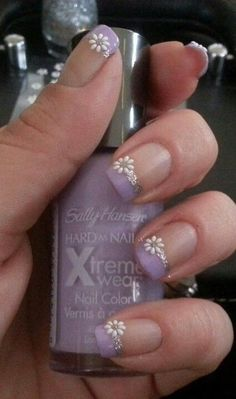 A cute Purple nail art design in French tips. Make your French tips stand out by adding pretty floral designs at the side in white embellishments and glitter polish. Nail Design, Nail Art, Nail Salon, Irvine, Newport Beach