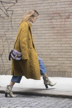 A teddy coat paired with jeans and snakeskin booties.