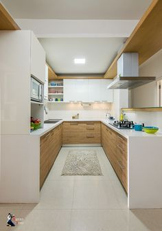 A U-shaped modular kitchen design with minimal handles, wood veneers finished with white laminates // simple modular kitchen design with white countertops and cabinets Kitchen Design Open, Kitchen Cabinet Design, Kitchen Layout, Interior Design Kitchen, U Shaped Kitchen Interior, Moduler Kitchen, Kitchen Laminate, Kitchen Cabinets, Small Modern Kitchens