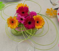 Tuintafel versieren met bloemen in glazen potjes is eenvoudig maar mooi met gekleurd steekschuim en pitriet