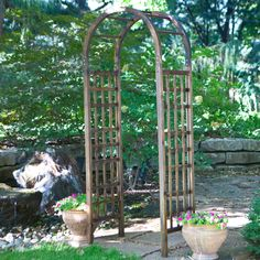 This would fit, and it's wood, would probably go with the fence.... Coral Coast 7.5 ft. Arched Wood Arbor - $149.99 @hayneedle.com.com