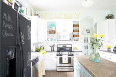 I love everything about this DIY kitchen makeover! From the chalkboard fridge to the painted cabinets - kitchen looks so much more open and bright.