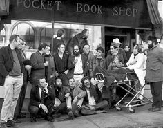 City Lights Bookstore • Dec. 3, 1965 • Literature Poets of S.F., circa 1965. Conclave of poets assembled at City Lights. Upper Top Row: Stella Levy, Lawrence Ferlinghetti. Second standing row: Donald Schenker, Michael Grieg, unknown person, Mike Gibbons, David Miltger, Michael McClure, Allen Ginsberg, Dan Langton, Steve Brostan, Gary Goodraw and son Homer, Richard Brautigan (in back of Goodrow). Seated: unknown person, Shig Murao, Lew Welch, Peter Orlovsky. PETER BREINIG/THE CHRONICLE 1965