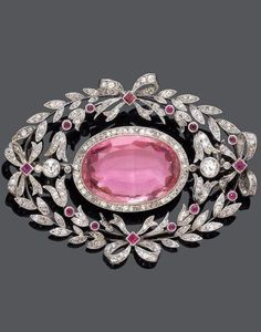 A BELLE ÉPOQUE TOPAZ, RUBY AND DIAMOND BROOCH, ca. 1910. An openwork brooch set with one oval pink topaz, probably not heated, within a diamond surround, with a laurel leaf and ribbon bow wreath frame, set with circular- and rose-cut diamonds, and further set with 14 small rubies, mounted in platinum. #BelleEpoque #brooch