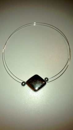 Double aspect choker. Ends covered by grey glass pearl-type beads. Large silver coloured bead sits in the base of the neck.
