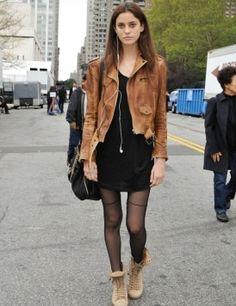 Vestido negro con medias a juego, una chaqueta de cuero caramelo y unos botines de color ocre claro, un bolso negro y un collar largo.