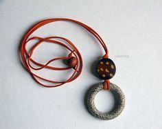 Collana con pendente a cerchio. Collana lunga. Beige, marrone, arancione.