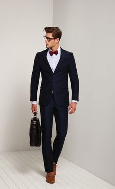 dark blue suit. crisp white oxford. red bow tie. brown suede loafers. dark brown leather briefcase . sharp. sophisticated. style.