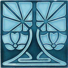 An Art Nouveau low relief tile with stylised double flower and stem design in light blue on a dark steel...