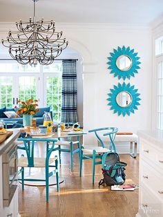 In the breakfast area, turquoise blue mirrors from a local vintage shop and wishbone chairs painted blue put a fresh spin on the familiar. Above the table, a traditionally-shaped chandelier gets a modern update, thanks to a chrome finish.