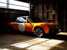 Porsche 914 looking resplendently orange in a shed
