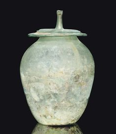 A ROMAN GREEN GLASS CINERARY URN CIRCA 1ST-2ND CENTURY A.D.