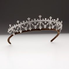 An *articulated* swag and drop fringe tiara set with brilliant cut Swarovski crystals mounted on a palladium plated bronze frame.