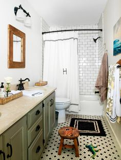 This charming bathroom's black and white penny tile floor and white subway tile shower add subtle style to this space. A sage green vanity lends muted color to the white room.
