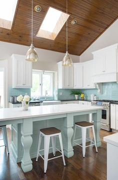 Tiffany blue kitchen features a vaulted ceiling framing skylights accented with a pair of mercury glass dome pendants illuminating a tiffany blue island fitted with turned legs topped with white quartz lined with white Tolix Stools.