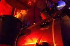 Baterísta y batería en tonos rojos.