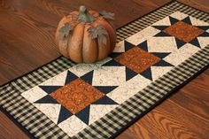 This black checked homespun table runner with patchwork stars is perfect for fall and Halloween decorating. Its a versatile addition to your dining table or cupboard. Size: 31 x 13 I used an orange print and a black print in the star blocks. The background fabric is a tan and black print. The outer binding and backing are solid black. I machine quilted an overall meandering stitch over the star blocks and a straight outline stitch in the homespun border. The batting is 100% cotton. It was…