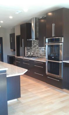 Marla Baird contemporary kitchen within dark cabinets, light wood floors and white tone countertop
