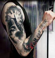 Sleeve tattoo by Simone Pfaff and Volko Merschky. The tattoo looks very creative as there is the clock on top with a hand seemingly reaching for it while the design dwindles downward unto the arm in what looks like a tower design.