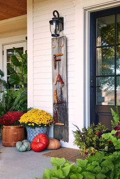 """For this project, glue corn cobs to a piece of rescued wood to spell out the word """"fall."""" Attach rope to hang your creation or simply lean it next to your front door. Finish the display with potted mums and plenty of pumpkins. #falldiy #walldecor #fallhomedecorideas #crafts #diyhomedecor #bhg Wood Picture Frames, Picture On Wood, Outdoor Wall Sconce, Outdoor Walls, Potted Mums, Diy Projects Cans, Fall Projects, Fall Door Decorations, Front Door Decor"""