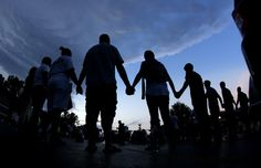 People stand in prayer after marching about a mile to the police station to protest the shooting of Michael Brown Wednesday, Aug. 20, 2014, in Ferguson, Mo. Brown's shooting in the middle of a street Aug 9, by a Ferguson policeman has sparked a more than week of protests, riots and looting in the St. Louis suburb.