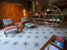 O tom lúdico do espaço ficou por conta do painel e das estantes que remetem a colmeias combinadas com pequenas mesas de metal coloridas Foto: Mauro Pimentel  / Terra