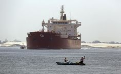 AP-  Aug. 12, 2014 file photo, Egyptian fishermen fish in front of a Maltese ship crossing the Suez Canal in Ismailia, Egypt.