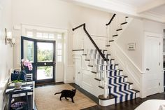 entry design w/navy blue door; navy & white striped stair runner
