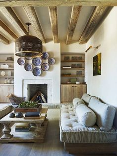 Cozy DIY sofa, wood beamed ceiling & plate wall above fireplace
