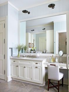 Antique sconces hang above the oversize mirror and add unexpected flair to the light and bright bathroom. The dark finish on the light fixtures adds weight to the room and helps unify the dark legs of the chair and the cabinet hardware. Their position above the vanity also provides task lighting for makeup application and grooming.