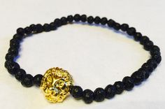 This is a very cool bracelet that is handmade in the USA as all of our items are. The Tibetan style lion head is a shiny gold color made of alloy. The beads are natural lava gemstones (black). This bracelet will stretch to fit. May this bracelet bring you peace and healing within as well as strength and courage. A portion of each bracelet sold will go to the St. Jude Childrens Research Hospital. This bracelet is made by jj stevens, a family owned and operated fashion line. Made in the USA…