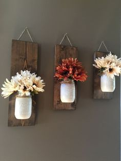 Short wooden planks with jars for flowers – cute wall decor!