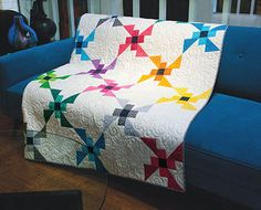 Colorful Propeller Blocks sparkle on a white background in this modern take on the repeating block design. The Flying Colors large lap size quilt is fast and easy to piece and makes a bold statement in any room.