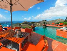 Beautiful view of the sea from this crimson patio.  Risingbarn.com #pool #red #orange #vibrant #colorful #outdoor #pool #oceanview #view #clear  #umbrella #sky