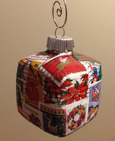 Glass ornament decoupaged with cancelled postage stamps.
