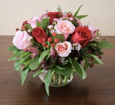 Table centerpiece with alstroemerias, roses, hypericum berry and wax.