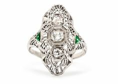 Exeter is an intricately designed antique Edwardian engagement ring featuring three Old Mine cut diamonds, accented by two triangular cut emeralds. How unique! TrumpetandHorn.com | $2,850