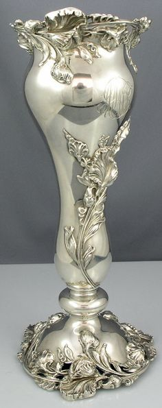 A sterling silver flower vase with applied three dimensional art nouveau flowers on the pedestal base, center and lip.