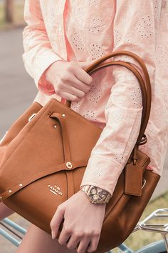 For work and play, from summer to fall: the Coach Turnlock Tie Tote in saddle brown leather pairs perfectly with whites and brights.