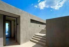 Con corte interna tipicamente mediterranea, la villa marina di Kea ha una scala in calcestruzzo che conduce al rooftop panoramico da cui godersi la vista e prendere il sole su semplici sdraio in tela