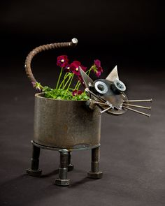 Made of recycled industrial scrap metal, this cow planter will fit standard medium size pots (~6-7). The planter will drain water out the bottom.