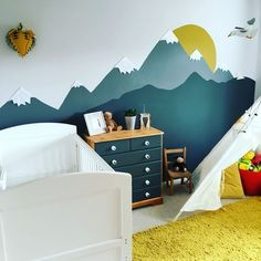 Mountain mural kids room in mustard yellow and grey. Dark grey is Farrow and Ball Downpipe grey. Yellow is Habitat. Rug from BQ. Teepee from Hobbycraft. Handprinted walls and refurbished drawers.