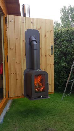 vesta-fire-exit-custom-wood-stove-05 Outdoor-Indoor install on a specially made safety hinged door. It swings out into the garden to warm the as-yet built deck-patio structure.
