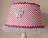 De simples abats-jours vichy rose et blanc customisés avec un peu de tulle, du ruban-serpentin et un ange en céramique. Outils nécessaires : une aiguille à coudre, une paire de ciseaux et un pistolet à colle.